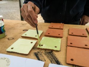 Participant painting handmade tiles